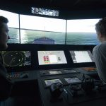Kaksi opiskelijaa ohjaa laivaa merenkulun komentosiltasimulaattorissa. Opiskelijat istuvat ohjauspöydän äärellä, jossa ohjausnäkymässä olevia ruutuja. Taustalla simulaattorin laivanäkymä, jossa laivan keula ja merimaisema.