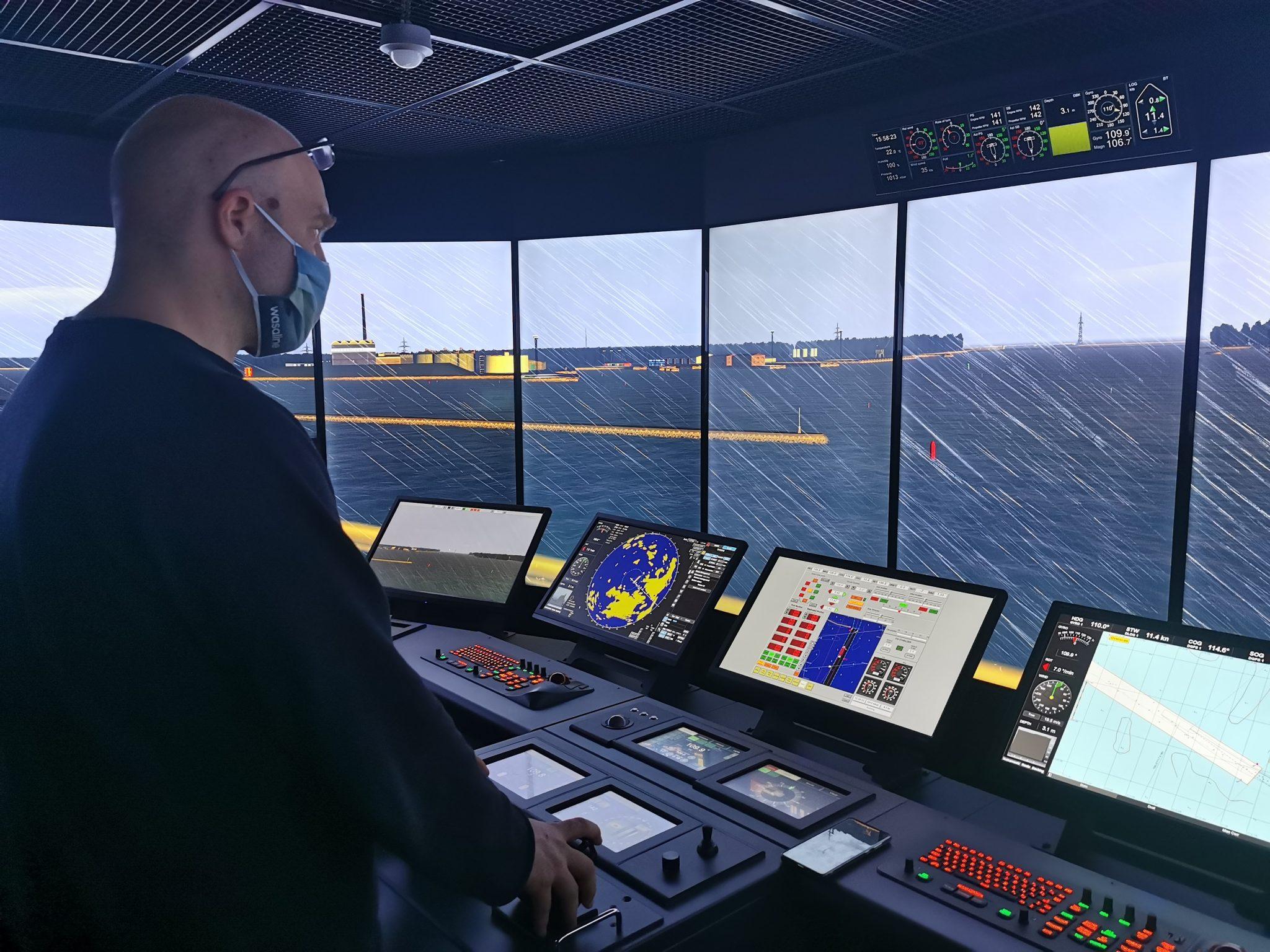 Yhteiskäyttösimulaattorit Kapteeni ohjaa laivaa merenkulun komentosiltasimulaattorissa. Näytöillä näkyy sateinen satamanäkymä.