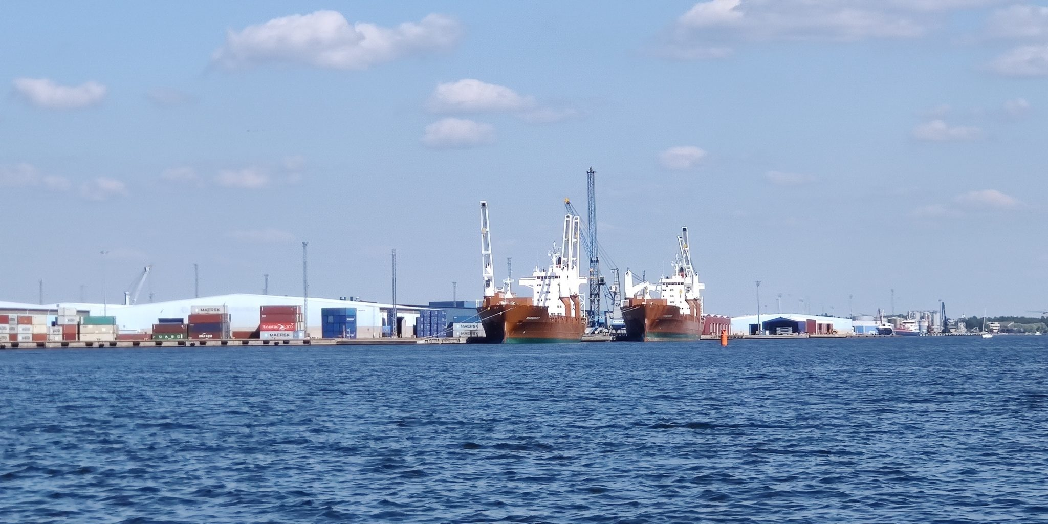 Harbor image with the sea in the foreground and ships being loaded in the background.